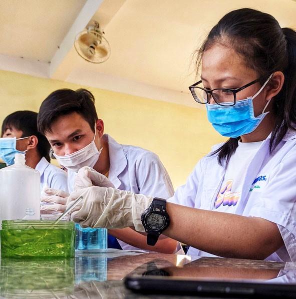 Các thành viên CLB STEM điều chế nước rửa tay diệt khuẩn tại phòng thí nghiệm của nhà trường.